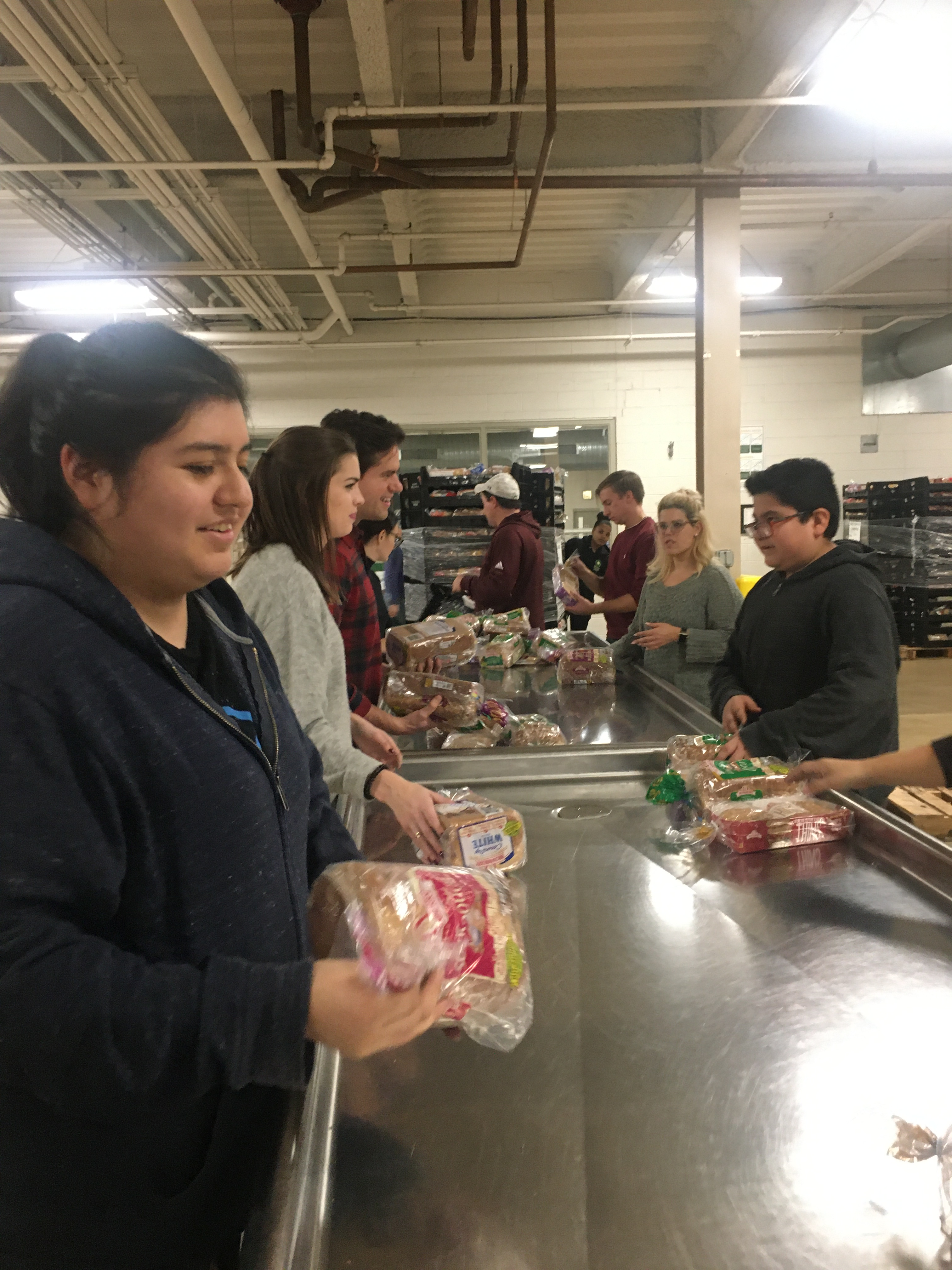 Volunteers perform quality checks on packages of bread